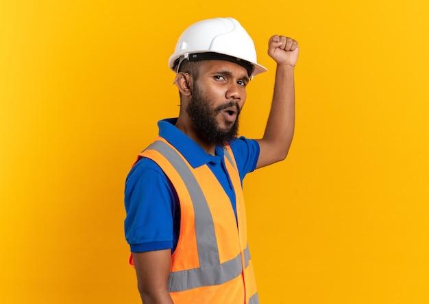 안전 헬멧을 쓴 제복을 입은 불쾌한 젊은 건축업자가 복사 공간이 있는 주황색 벽에 고립되어 주먹을 들고 있다