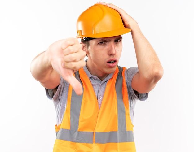 Un giovane costruttore scontento in uniforme che mostra il pollice giù mettendo la mano sulla testa