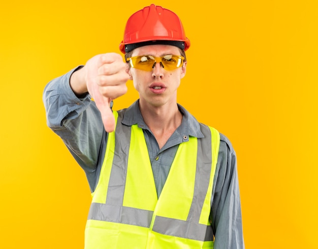 Unpleased young builder man in uniform wearing glasses showing thumb down