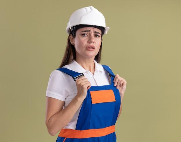 不機嫌な若いビルダーの制服を着た女性がオリーブ グリーンの壁に隔離された制服をつかんだ