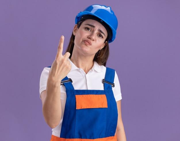 Donna giovane costruttore dispiaciuto in uniforme che mostra uno isolato sulla parete viola