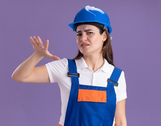 Giovane donna scontenta del costruttore in uniforme che mostra le dimensioni isolate sulla parete viola
