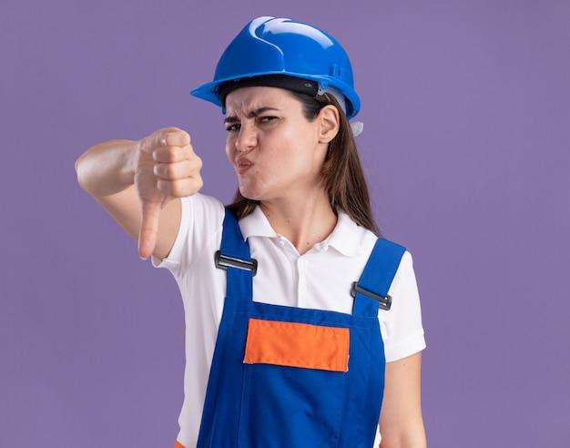 Una giovane donna scontenta del costruttore in uniforme che mostra il pollice verso il basso isolato sul muro viola