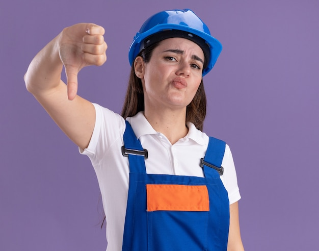 Unpleased young builder woman in uniform showing thumb down isolated on purple wall