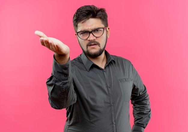ピンクで隔離のカメラに手を差し伸べて眼鏡をかけている不機嫌な青年ビジネス