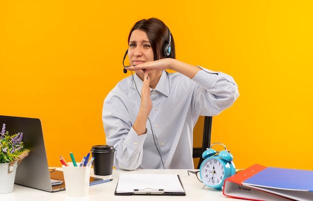 オレンジ色の背景に分離されたタイムアウトジェスチャーを行う作業ツールと机に座っているヘッドセットを身に着けている不機嫌な若いコールセンターの女の子
