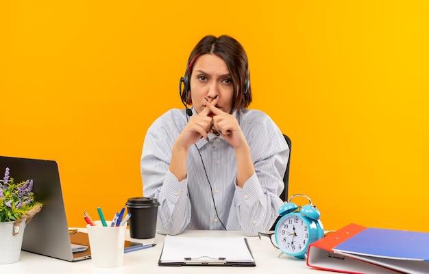 Soddisfatta giovane ragazza della call center che indossa la cuffia avricolare seduto alla scrivania con strumenti di lavoro che non fa alcun gesto isolato su sfondo arancione