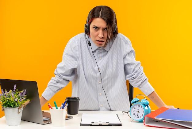 Недовольная молодая девушка колл-центра в гарнитуре стоит из-за стола с рабочими инструментами, изолированными на оранжевом фоне
