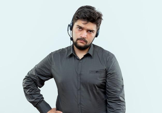 흰색에 고립 된 엉덩이에 손을 넣어 헤드셋을 착용 불쾌 젊은 콜 센터 남자