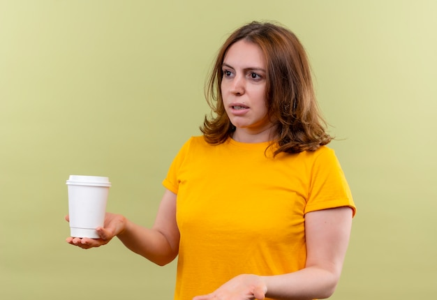 Giovane donna casuale dispiaciuta che tiene la tazza di caffè di plastica e che mostra la mano vuota sulla parete verde isolata