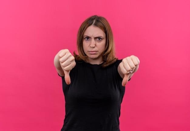 복사 공간이 격리 된 분홍색 벽에 아래로 엄지 손가락을 보여주는 불쾌한 젊은 캐주얼 여성