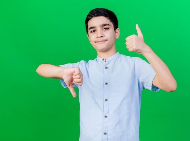 緑の背景に分離された親指を上下に示すカメラを見て不機嫌な若い白人の少年