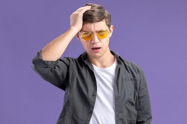 Unpleased young caucasian boy in sun glasses putting hand on his head and looking at camera