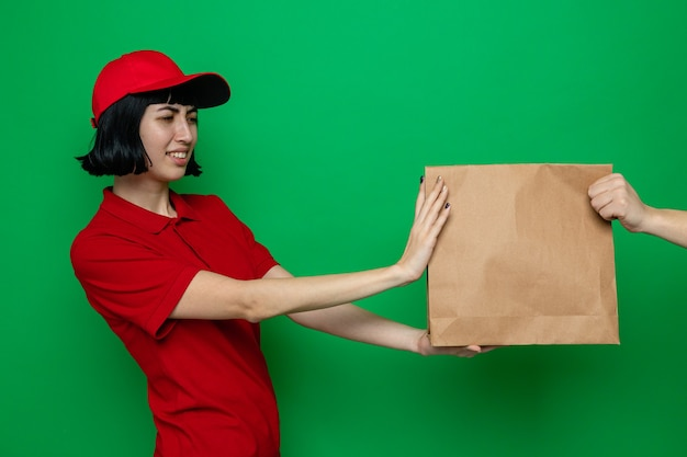 Unpleased young caucasian delivery girl giving paper food packaging to someone