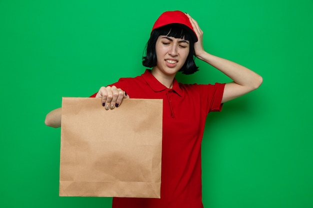 Unpleased young caucasian delivery girl holding and looking at paper food packaging