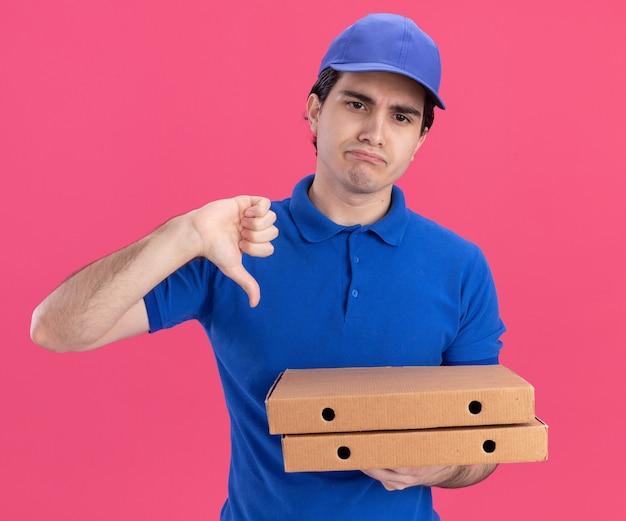 Giovane fattorino caucasico scontento in uniforme blu e berretto che tiene in mano i pacchetti di pizza guardando dritto mostrando il pollice verso il basso
