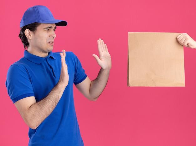Giovane fattorino caucasico scontento in uniforme blu e berretto che guarda di lato facendo un gesto di rifiuto e qualcuno che allunga il pacchetto di carta a lui
