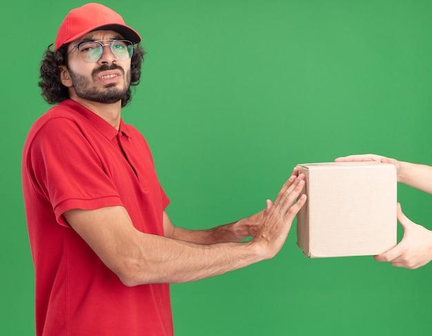 Недовольный молодой кавказский доставщик в красной форме и кепке в очках, стоящий в профиль, давая картонную коробку клиенту, толкающему ее