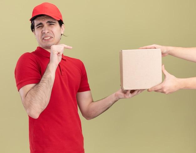 Giovane fattorino caucasico scontento in uniforme rossa e berretto che dà una scatola di carte al cliente che punta alla scatola
