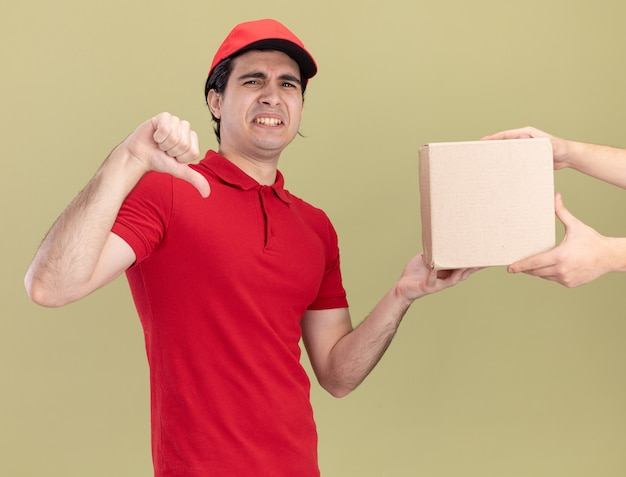 Unpleased young caucasian delivery man in red uniform and cap giving cardbox to client showing thumb down