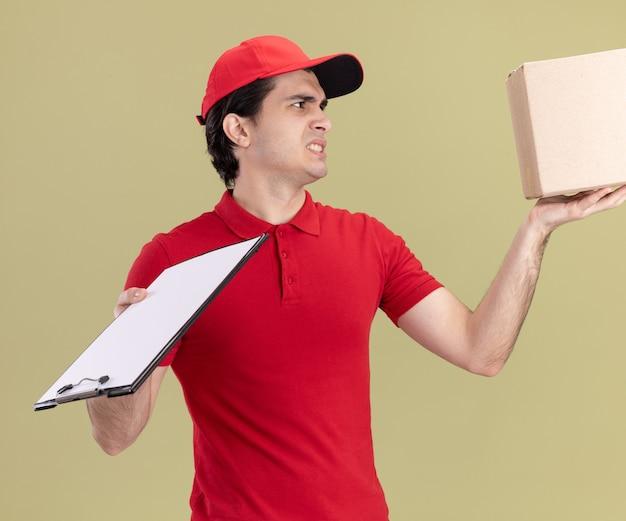 Giovane fattorino caucasico scontento in uniforme rossa e berretto con scatola di cartone e appunti guardando la scatola