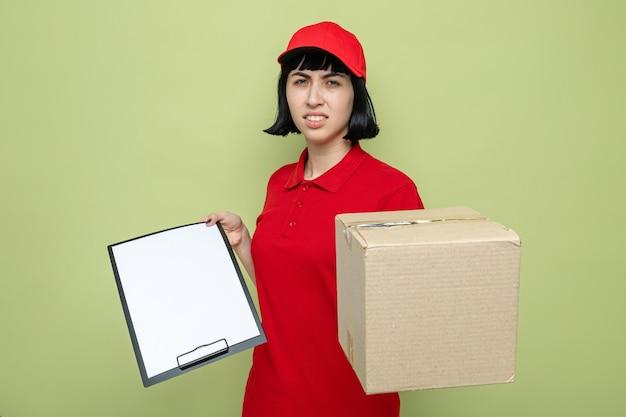 Недовольная молодая кавказская женщина-доставщик, держащая картонную коробку и буфер обмена