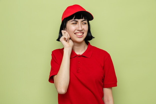 Unpleased young caucasian delivery woman holding her ear and looking at side