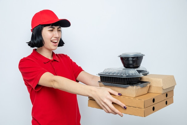 Unpleased young caucasian delivery woman holding and looking at food containers with packaging on pizza boxes