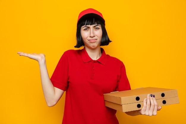 Giovane donna delle consegne caucasica scontenta che tiene in mano scatole per pizza e tiene la mano aperta
