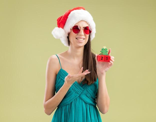 Недовольная молодая кавказская девушка в солнцезащитных очках в шляпе санта-клауса держит и указывает рукой на украшение рождественской елки