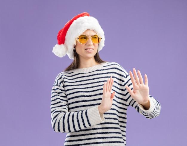 산타 모자와 태양 안경에 불쾌한 젊은 백인 여자 보유 손을 보유하고 측면을보고 흔적이없는 몸짓