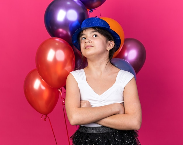 Unpleased young caucasian girl with blue party hat standing with crossed arms in front of helium balloons looking up isolated on pink wall with copy space