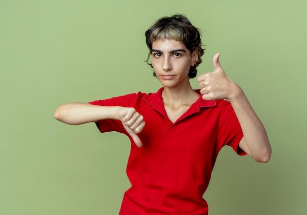 Giovane ragazza caucasica dispiaciuta con taglio di capelli di pixie che mostra i pollici su e giù isolati su priorità bassa verde oliva