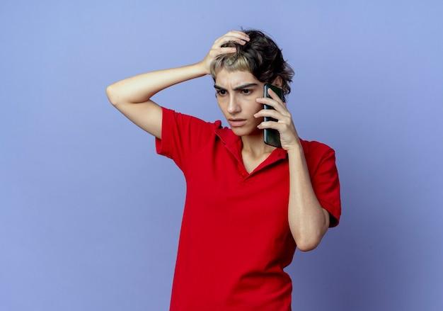 コピースペースと紫色の背景で隔離の頭に手を置いて電話で話しているピクシーの散髪を持つ不機嫌な若い白人の女の子