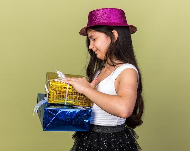 Scontenta giovane ragazza caucasica con cappello da festa viola che tiene e guarda scatole regalo isolate su parete verde oliva con spazio di copia copy