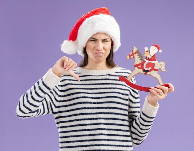 サンタの帽子をかぶった不機嫌な若い白人の女の子は、ロッキングホースの装飾にサンタを保持し、コピースペースで紫色の背景に分離された親指