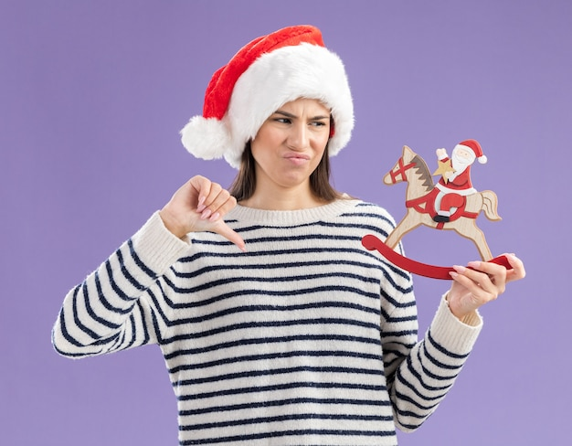 Unpleased young caucasian girl with santa hat thumbs down holding and looking at santa on rocking horse decoration isolated on purple wall with copy space