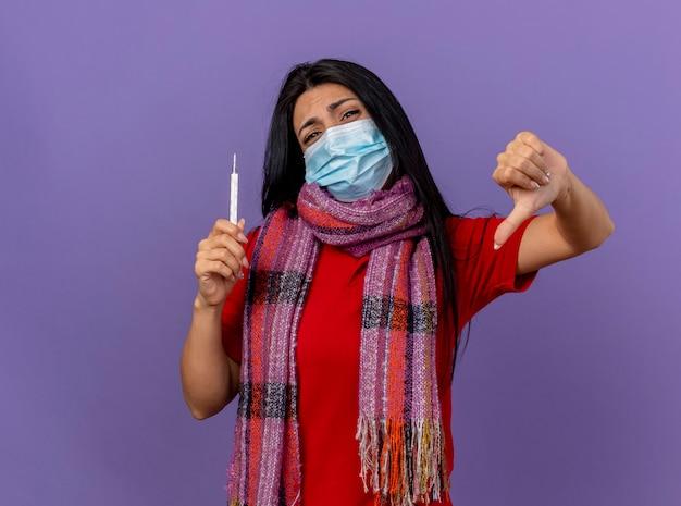 コピースペースと紫色の壁に分離された親指を下に示す温度計を保持しているマスクとスカーフを身に着けている不機嫌な若い白人の病気の女の子