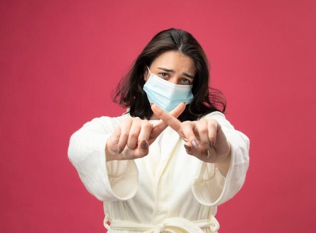 真っ赤な背景で隔離されたジェスチャーをしないカメラを見てローブとマスクを身に着けている不機嫌な若い白人の病気の女の子
