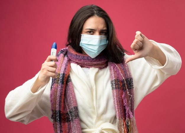 真っ赤な壁に隔離された親指を下に示す温度計を保持しているマスクとローブとスカーフを身に着けている不機嫌な若い白人の病気の女の子