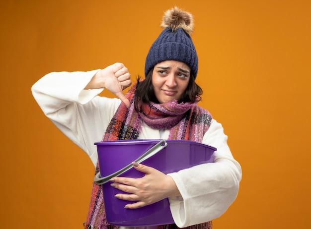 Недовольная молодая кавказская больная девушка в зимней шапке и шарфе, испытывающая тошноту, держит пластиковое ведро, глядя в сторону, показывая большой палец вниз, изолированную на оранжевой стене с копией пространства