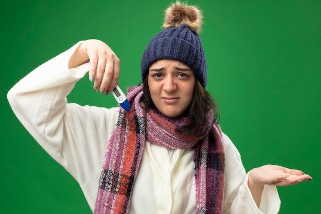 녹색 배경에 고립 된 카메라를보고 빈 손을 보여주는 온도계를 들고 가운 겨울 모자와 스카프를 착용 불쾌한 젊은 백인 아픈 소녀