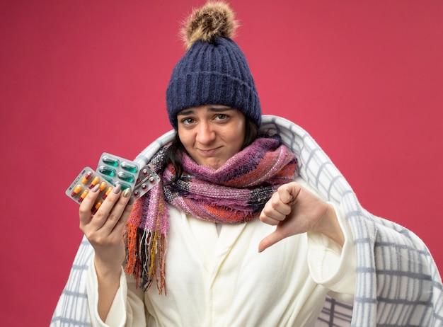 真っ赤な背景に分離された親指を下に向けてカメラを見ているカプセルの格子縞の保持パックに包まれたローブの冬の帽子とスカーフを身に着けている不機嫌な若い白人の病気の女の子