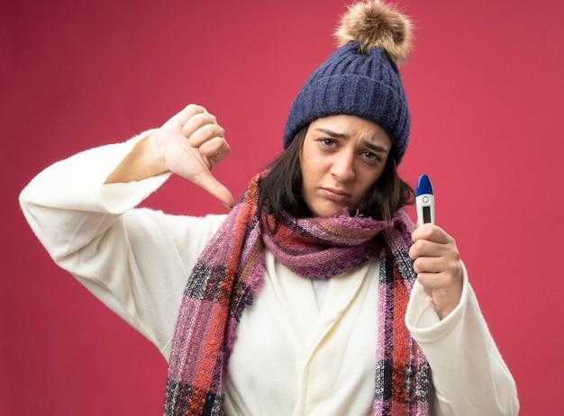 Felice giovane indoeuropeo ragazza malata indossando robe inverno cappello e sciarpa tenendo il termometro guardando la telecamera che mostra il pollice verso il basso isolato su sfondo cremisi
