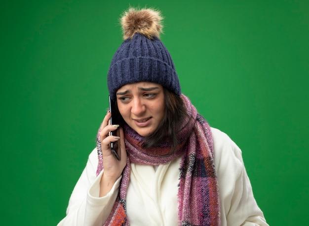 Ragazza malata caucasica giovane dispiaciuta che indossa il cappello e la sciarpa di inverno della veste che comunicano sul telefono che esamina il lato isolato su fondo verde