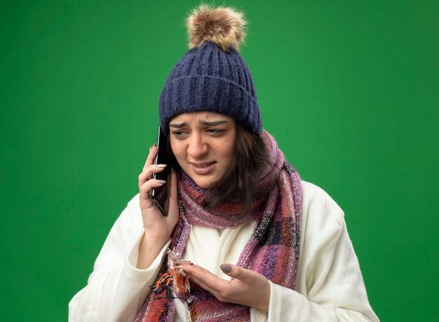 Giovane ragazza malata caucasica dispiaciuta che indossa il cappello e la sciarpa di inverno della veste che comunicano sul telefono che mostra la mano vuota che esamina il lato isolato sulla parete verde