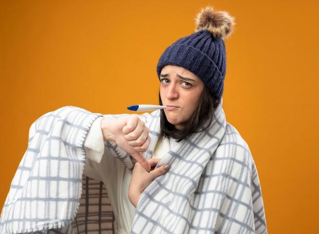 オレンジ色の背景に分離された親指を下に示している口の温度計でカメラを見て格子縞に包まれたローブの冬の帽子をかぶっている不機嫌な若い白人の病気の女の子