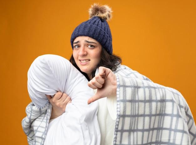 オレンジ色の背景に分離された親指を下に表示しているカメラを見て枕を抱き締める縦断ビューで立っている格子縞に包まれたローブの冬の帽子を身に着けている不機嫌な若い白人の病気の女の子