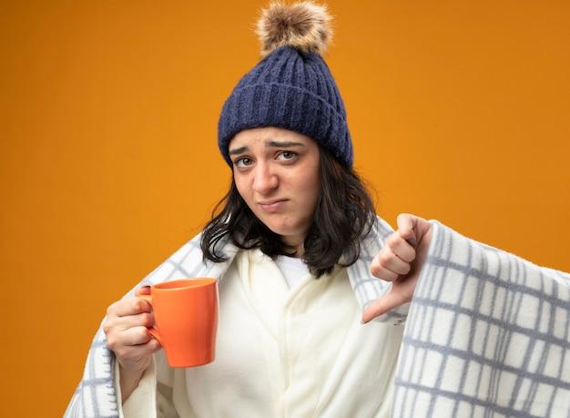 Felice giovane indoeuropeo ragazza malata indossando robe cappello invernale avvolto in plaid tenendo la tazza di tè guardando la telecamera che mostra il pollice verso il basso isolato su sfondo arancione