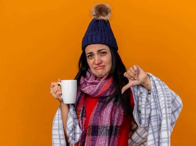 겨울 모자와 스카프를 착용하는 불쾌한 젊은 백인 아픈 소녀 복사 공간이 오렌지 벽에 고립 된 엄지 손가락을 보여주는 체크 무늬 차 한잔에 싸여